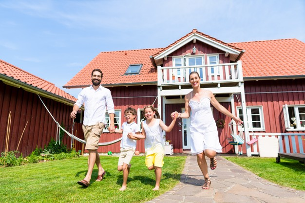 happy-family-running-meadow-front-house-front-yard-grass_79405-13856