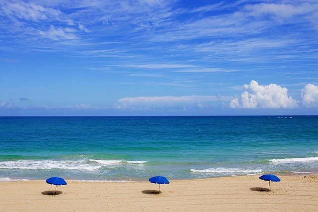 Piesková pláž s troma modrými slnečníkmi.jpg