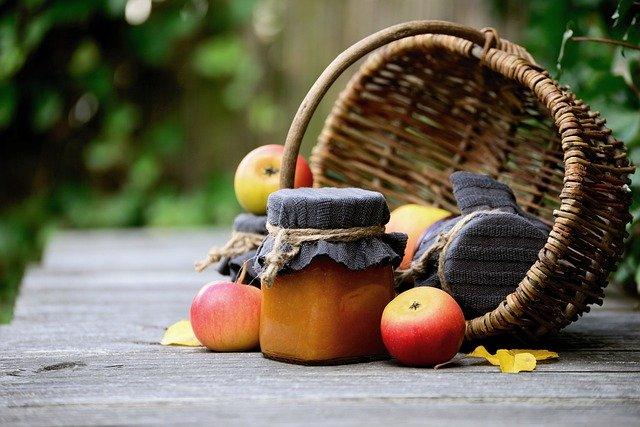 Prútený košík s jablkami a zaváraninami na drevenom stole