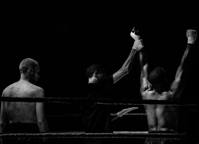 Rozhodca drží ruku víťazovi v boxerskom ringu.jpg
