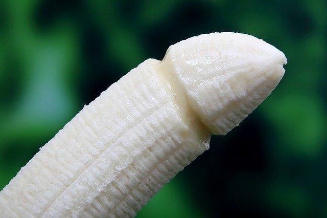 Banána v tvare penisu na zelenom pozadí
